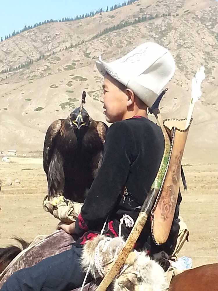 A young Kyrgyz falconer, on his horse for travelling the steppes.